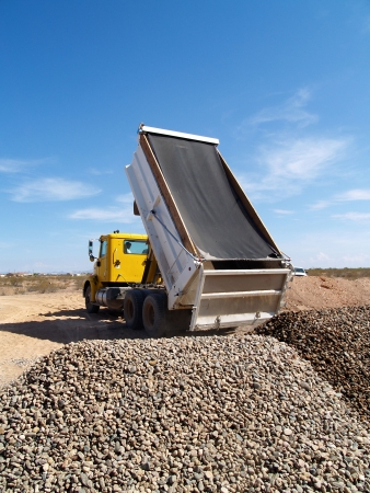 A dump truck is dumping gravel on an excavation site.   Vertically framed shot. Stock Photo