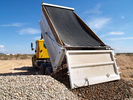 A dump truck is dumping gravel on an excavation site.   Horizontally framed shot.