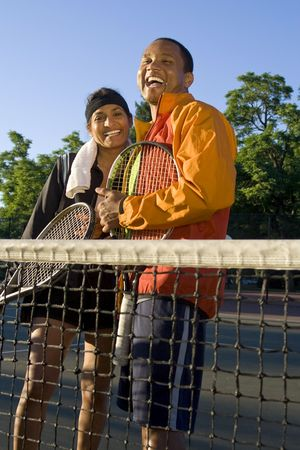 Tennis couple standing at the net holding their rackets and laughing. Vertically framed photo.