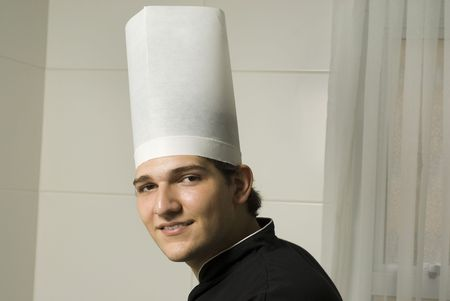 Smiling young chef in a chef's hat . Horizontally framed photo. photo