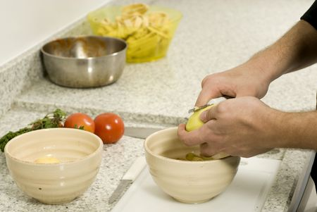Hands peeling potatoes into a bowl on a counter next to a bowl and tomatoes. Horizontally framed photo. Stock Photo - 3881892