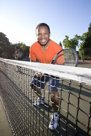Man playing tennis. He holds his racket and stands near the net as he smiles happily. Vertically framed photo. photo
