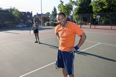 Smiling man with hands on hips standing on the tennis court, his teammate stands in the background holding her racket and smiling. Horizontally framed photo. photo