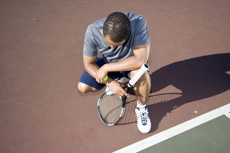 Tennis player crouched down in defeat. He is kneeling while holding his racket and ball. Horizontally framed photo.