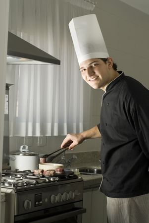 Young, smiling chef grilling steaks on a griddle on a stove in a kitchen. Vertically framed photo. photo