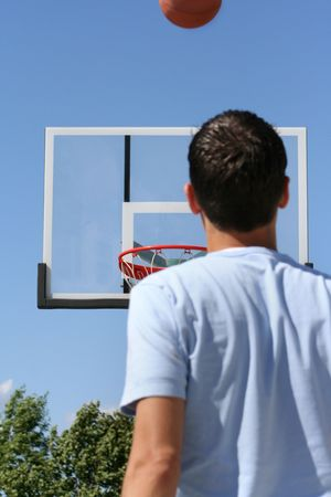 ascends: The rear view of a young boy facing a hoop as a basketball ascends toward it. Horizontally framed shot.