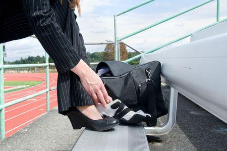 pista de atletismo: Mujer en un traje sentado en una Bleacher en una pista poniendo en funcionamiento un zapato. Horizontalmente foto enmarcada.