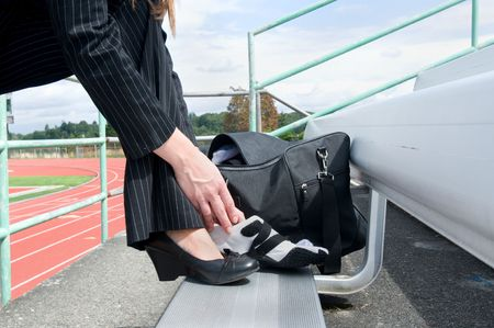 Woman in a suit sitting on a bleacher at a track putting on a running shoe. Horizontally framed photo. Stockfoto