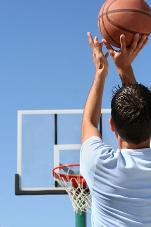 The rear view of a young boy shooting a basketball toward a hoop. Vertically framed shot.