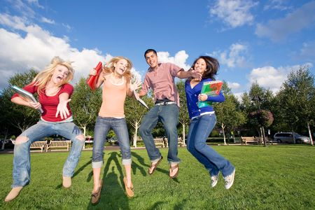 giggle: Four teen students carrying books, jumping and laughing outside. There is one boy and three girls. Horizontally framed photo. Stock Photo