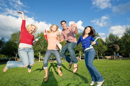 Four teen students carrying books, jumping and laughing outside. There is one boy and three girls. Horizontally framed photo. Stock Photo