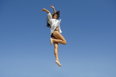 Young Mediterranean woman jumps freely between the meadows in the sky  photo