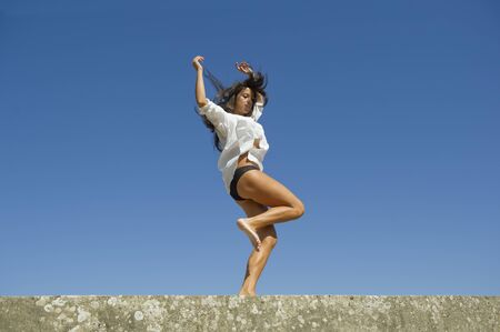 Young Mediterranean woman jumps freely between the meadows in the sky  Stock Photo