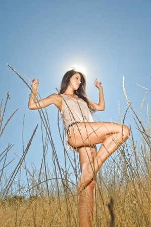 Against the sun - Young Mediterranean woman freely through the meadows  photo