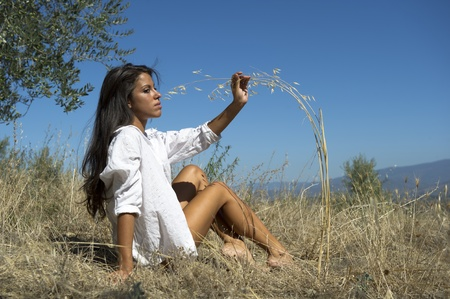 Young woman sitting in the grass in nature