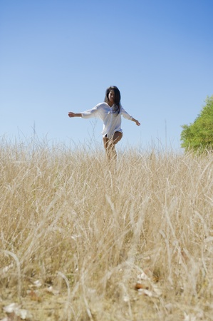 Mediterranean woman freely running through the meadows Stock Photo