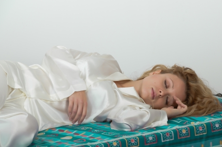 Young woman-girl in pajamas asleep lying on the soft mattress of his bed photo