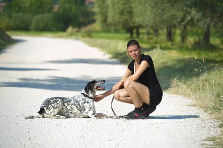 Girl cuddles her dog after a run in the meadows Stock Photo