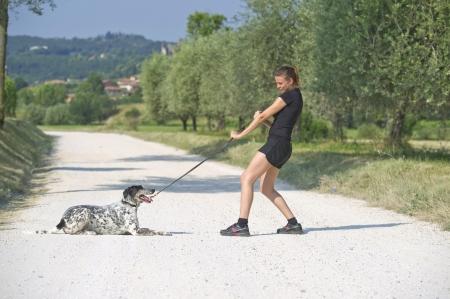 Gioco della ragazza tirando il suo cane al guinzaglio