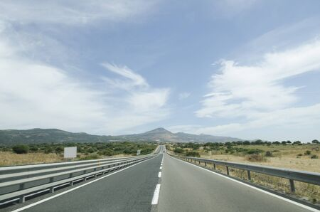 guard rail: Road – two lane highway  Photography taken from the machine  Blue sky and clouds in the background