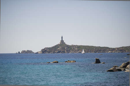 Sardinian sea and lighthouse on the cliff in the distance