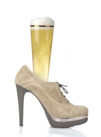Glass of beer in beige high-heeled shoe