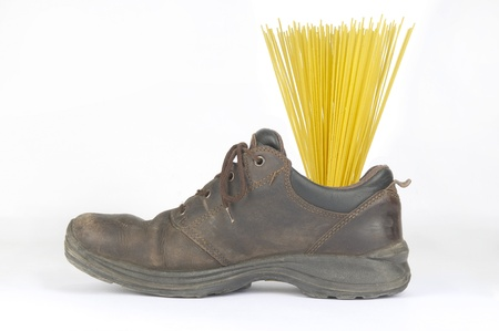 Portion of uncooked spaghetti in work shoes brown Imagens