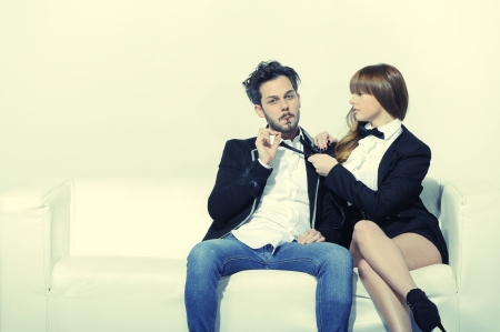 Young boy sitting on the white sofa with a cigar in his mouth while his girlfriend pulls him by the tie