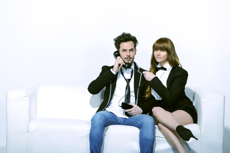 Boy with the phone in hand, sitting on the sofa with his girlfriend