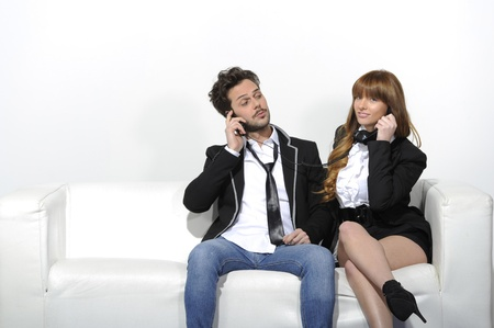 Girl with the phone in hand, sitting on the sofa with her boyfriend