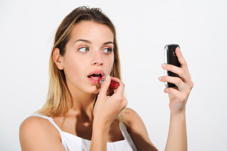 Beautiful girl puts on red lipstick on her lips as he reflected on his cell phone