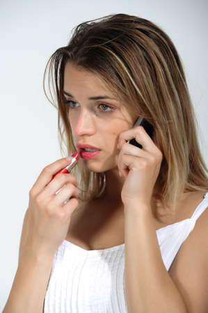 Closeup of a thoughtful young girl on the phone while you put lipstick on her lips