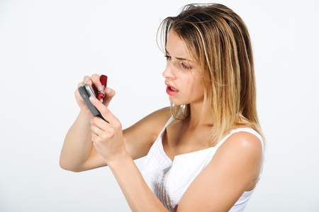 Closeup of a beautiful girl who writes on his cell phone with a red lipstick Stock Photo