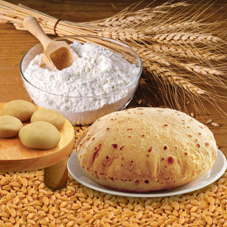 Wheat flour, Chapati, Roti, Bunch of wheat ears, dried grains, flour in terracota bowl. Cereals harvesting, bakery products. Stock fotó