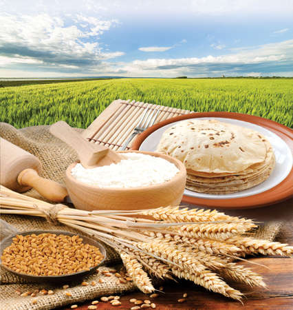 Wheat flour, Chapati, Roti, Bunch of wheat ears, dried grains, flour in terracota bowl on Wheat Farm background. Cereals harvesting, bakery products.