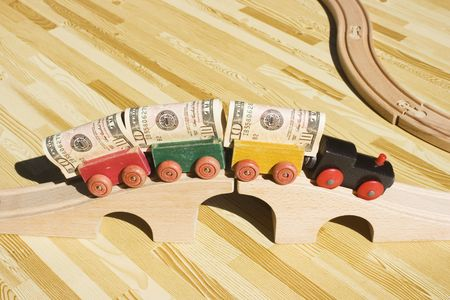 A toy train pulling a cargo of money and going over a bridge.  This picture could be a reference to 'bridging loan','money delivery', gravy train, cargo, freight.  Also, money supply and transfering money.