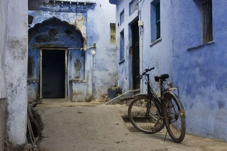A little blue alleyway that leads to an elaborate blue door.  Theres a bicycle and an old time feel.