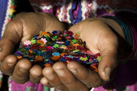 A handful of colour.  An Indian girl holds a handful of sewing beads that her tribes uses to make clothes and accessories. The beans are brightly coloured.