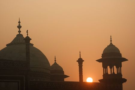 These are the domes and spires of the Jawab. This mirrors the mosque on the west side of the Taj Mahal but isnt used for prays as it faces away from Mecca. The light is early morning sun shining through mist.