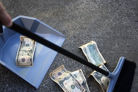 Sweeping up money.  Someone sweeping up 10 dollar bills off the ground.  A reference to collecting up money or sweep stakes photo