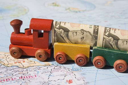 A toy train, loaded with US dollars going to North America.  The concept is trade between nations, international trade.  The train represents movement, the money transactions and the map, well the world. photo
