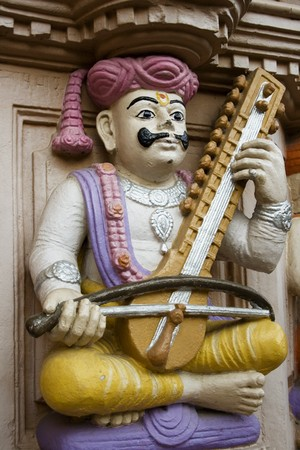A sculpture of a an Indian Musician. I'm unsure of the instrument.  It could be a sitar, though this often plucked. Esraj and dilruba are played with a bow.  This is part of the very colourful Swaminarayan Mandir temple complex in Ahmedabad. Stock Photo - 4112561
