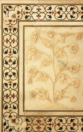 Some detail carvings or inlaids at the Taj Mahal.  The detail here is of a plant with flowers surrounded on three sides by a border. photo