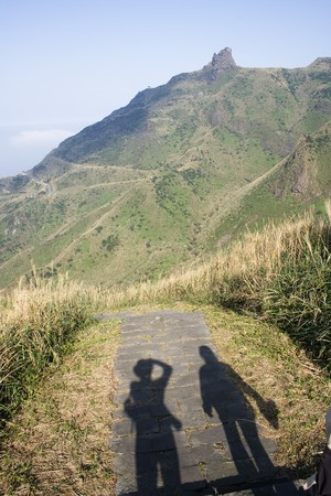 admire: A couple on a walk, stop and admire teapot mountain. So called, because the rocks on the top of the mountain look like a teapot.  This is in taiwan, a top tea producing nation and the picture could be used for the promotion of tea.