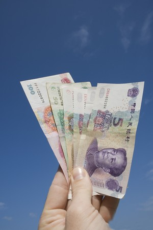 A buyer holds a range of Chinese notes in his hand.  He could be trading in China or looking at investments there.  Chinese currency is called the RMB or Yuan