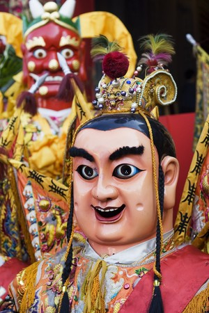 These are man-size puppets or costumes worn by temple workers during parades.  They are popular in Taiwan and are paraded on a regular bases.  They form a core part of Chinese Culture.  The red-face god in the background is thousand mile eyes, who with