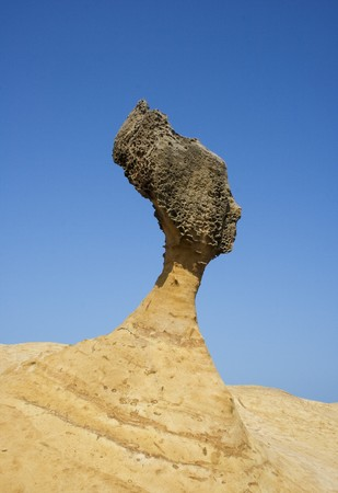 This rock looks like an Egyptian Queen.  Its at Yeliu, Taiwan.  There are many strange rock formations here.  Also looks like a chess piece. Stock Photo
