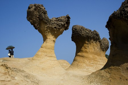 These are strange rocks formations at Yeliu, Taiwan. Theres a couple in the background, adding a romantic touch to the picture. Stock Photo