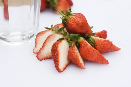 sweetness: Strawberries ready to eat.  They are on a table and in a glass of water.