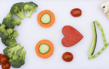 Vegetables have been used to make a happy face with a love heart as the nose.
